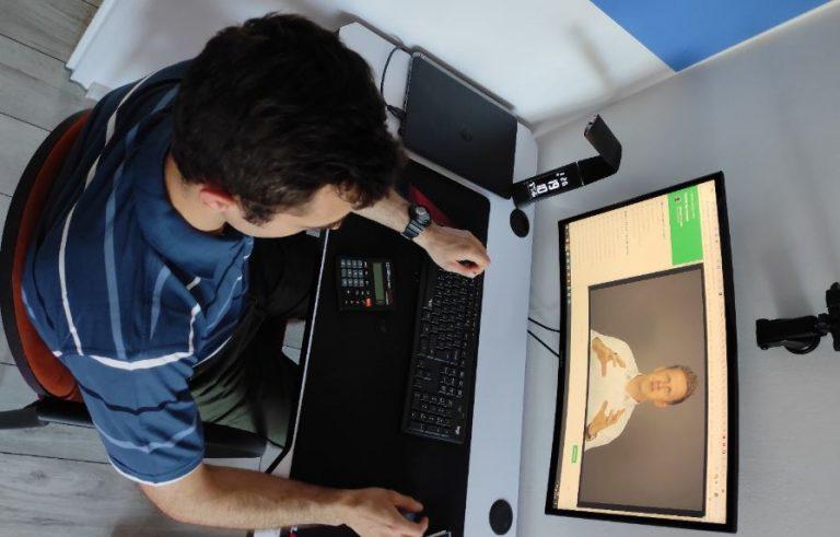 Przedsiębiorca przy komputerze, na którym widać jego nowy projekt strony internetowej.
